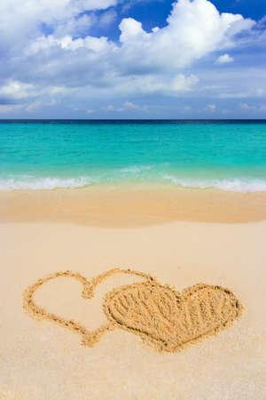 Dibujo corazones conectados en la playa, el amor concepto Foto de archivo