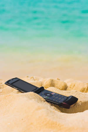 Mobile phone on sand beach, communication concept photo