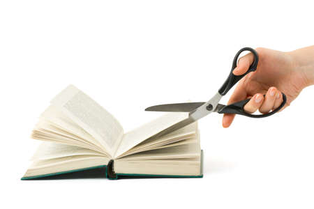 censor: Hand with scissors cutting book isolated on white background Stock Photo