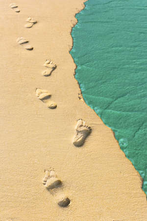 Foot steps and surf on tropical beach, abstract travel background photo