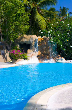 Pool and waterfall in hotel, vacation background photo