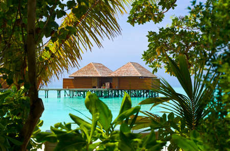 Water bungalows on a tropical island, vacation background photo