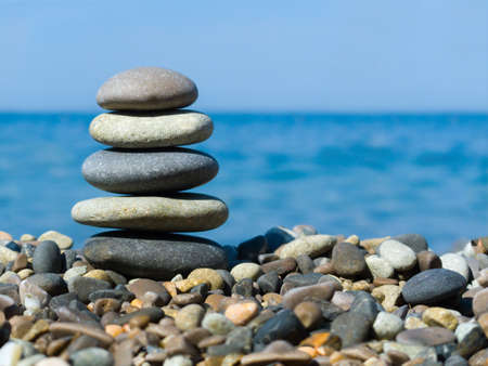 Stack of stones on beach, sea and sky photo