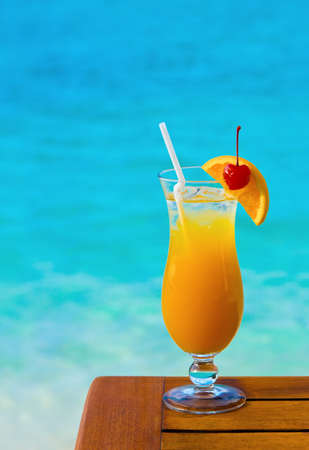 Orange cocktail on table, sea background photo