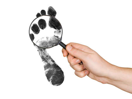 Magnifying glass in hand and foot printout isolated on white background photo