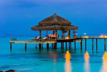 Water cafe at evening, lights, ocean and sky photo