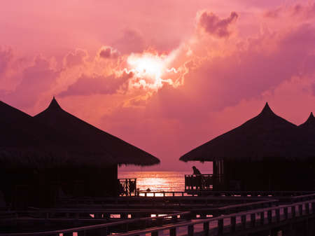 Human silhouette in water bungalow at sunset, abstract vacation background Stock Photo - 4681450