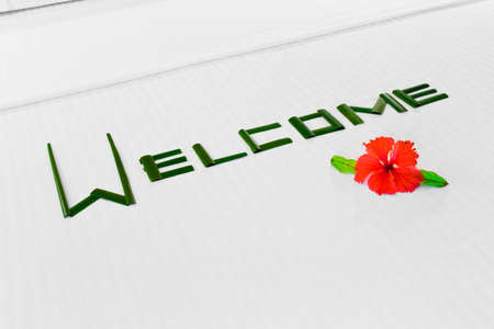 Word Welcome made of palm leafs and flower on bed photo