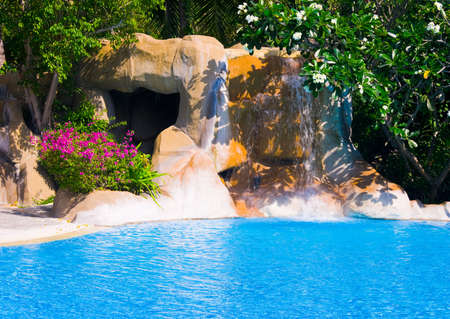 Pool and waterfall in hotel - vacation background