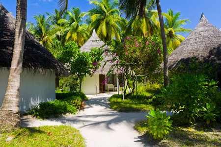 architecture bungalow: Bungalows and pathway, flowers and trees, vacation background Stock Photo