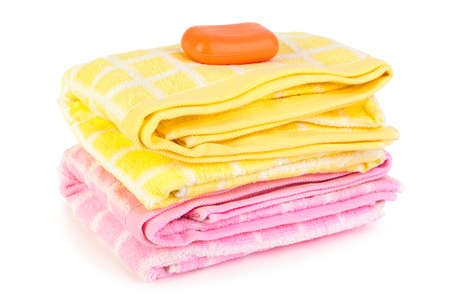 Towels and piece of soap isolated on white background photo