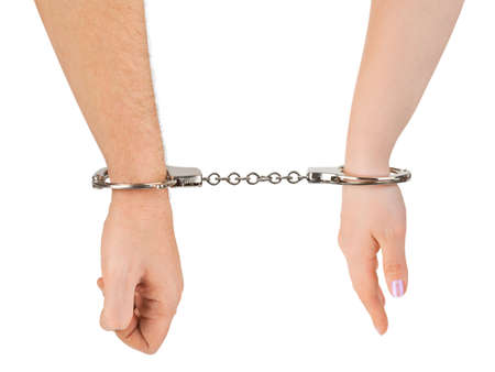 wristbands: Man and woman hands and handcuffs isolated on white background