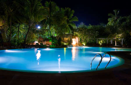 Pool and waterfall at night - vacation background photo
