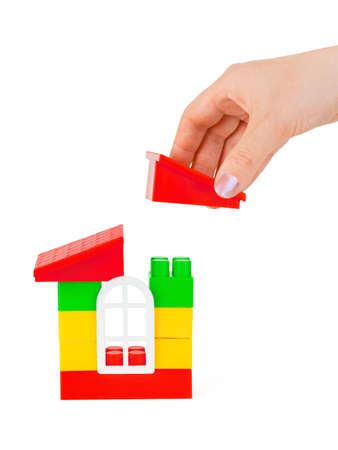Hand and toy house isolated on white background Stock Photo - 4863044