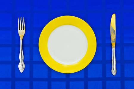 Plate, knife and fork on table cloth, food background photo