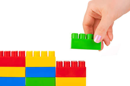 erector: Hand and toy wall isolated on white background