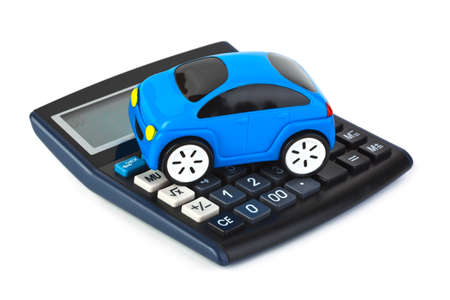 car loans: Calculator and toy car isolated on white background