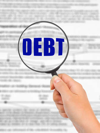 credit report: Magnifying glass in hand and word Debt, business background Stock Photo