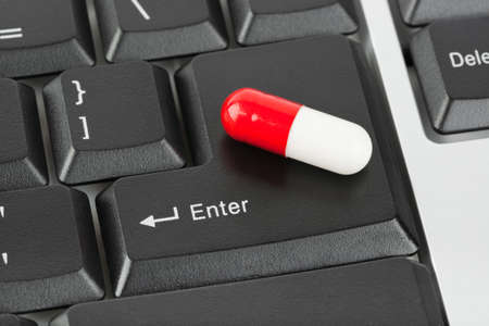 Pill on computer keyboard - concept technology background photo