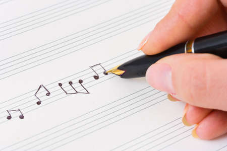Hand with pen and music sheet - musical background photo