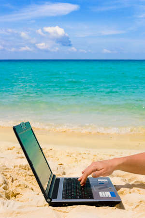 Computer and hand on beach, business travel background  Stock Photo