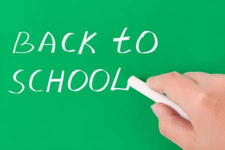 Hand with chalk writing Back to school on blackboard photo
