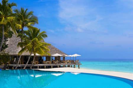 Caffè e la piscina su di una spiaggia tropicale - sfondo di viaggio