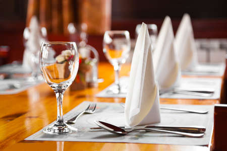 restaurant setting: Glasses and plates on table in restaurant - food background