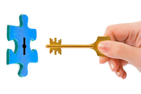 Hand with key and puzzle isolated on white background photo