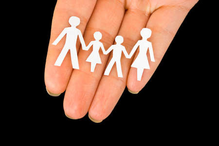 Paper family in hand isolated on black background photo