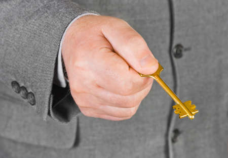 Man in suit and hand with key Stock Photo - 5786489