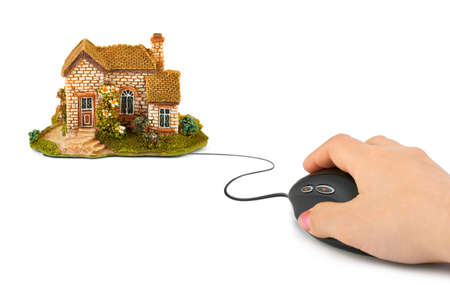 Hand with computer mouse and house isolated on white background photo