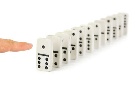 Finger and domino isolated on white background photo