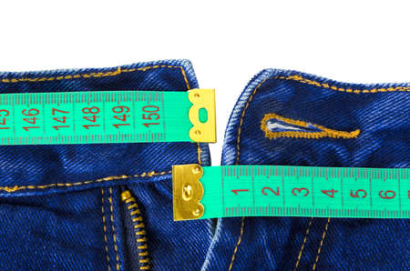 Jeans and measuring tape - sliming, isolated on white background photo