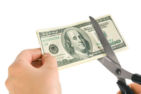 savings problems: Hands with scissors cutting money isolated on white background
