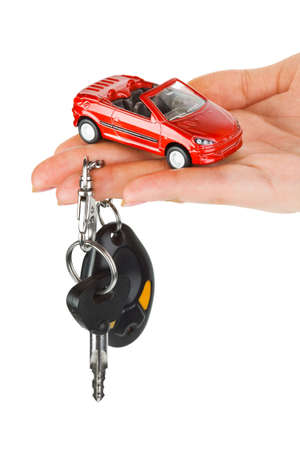 Hand with keys and car isolated on white background photo