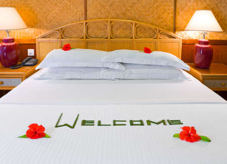 Word Welcome made of palm leafs and flowers on bed photo