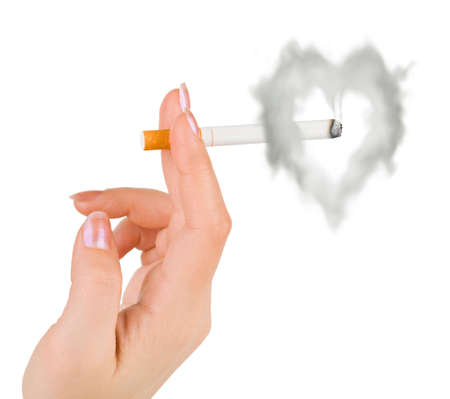 Hand with cigarette and heart shaped smoke isolated on white background photo