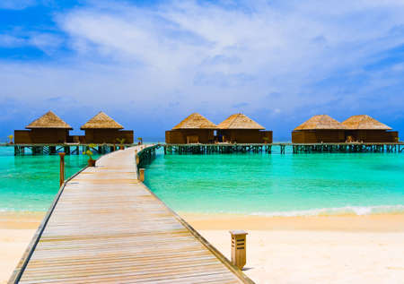 palapa: Water bungalows at a tropical island - travel background Stock Photo