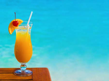 coctel de frutas: C�ctel naranja sobre fondo de tabla y mar