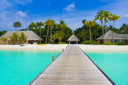 Beach bungalows on a tropical island - travel background Stock Photo