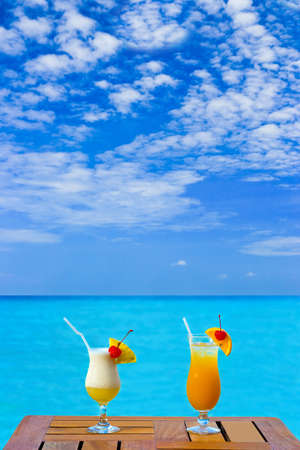 beach drink: Two cocktails on table, sea background