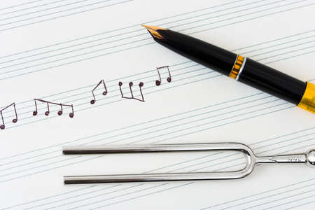 Pitchfork and pen on music sheet - abstract art background photo