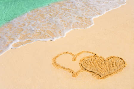 Drawing connected hearts on beach - love concept photo
