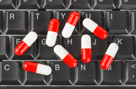 Pills on computer keyboard - concept technology background photo