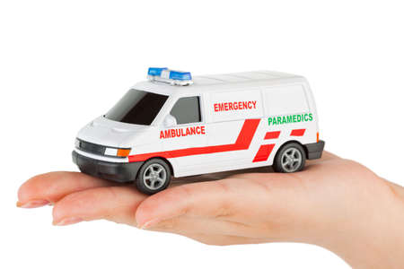 doctor toys: Hand with toy ambulance car isolated on white background