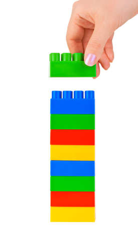 erector: Hand and toy tower isolated on white background