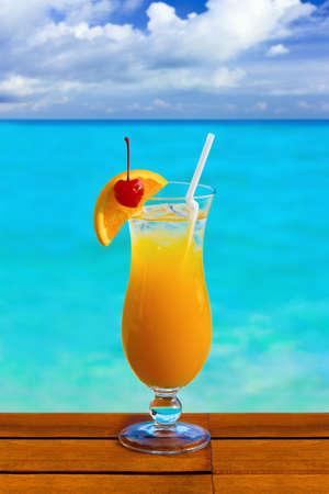 Orange cocktail on table, sea background photo