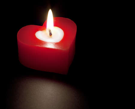 burning love: Heart shaped candle isolated on black background