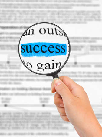 Magnifying glass in hand and word Success, business background photo